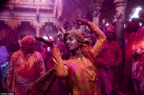 A Hindu worshippe dances with coloured paint on his body during Lathmar Holi