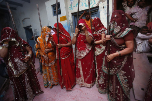 A group of women stand while holding sticks during Lathmar Holi at the village of Barsana